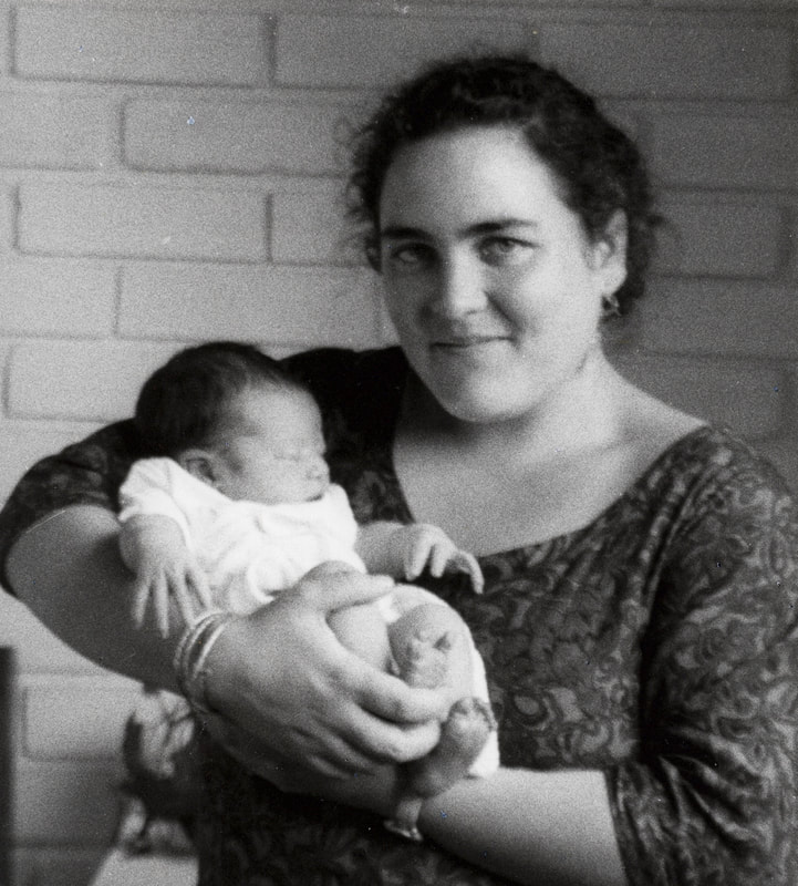 Naoli Vinaver holding a newborn baby who she was a midwife in childbirth