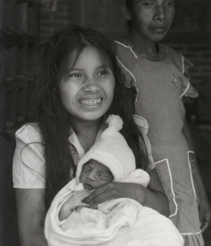 Natividad at the age of 15 holding her newborn baby with her mom in the background, days after she became a mother. In Rancho Viejo, Xalapa, Veracruz. Mexico
